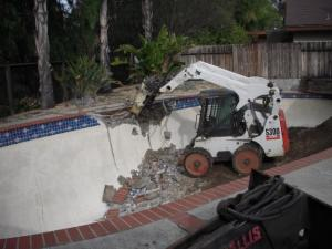 a professional tech is working with a small excavator on a Redwood City swimming pool removal job